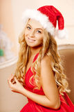 Young beautiful smiling santa woman near the Christmas tree. Gir Stock Photo