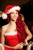 Young beautiful smiling santa woman near the Christmas tree. Gir Royalty Free Stock Photo