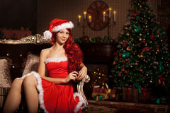 Young beautiful smiling santa woman near the Christmas tree. Gir Royalty Free Stock Photos