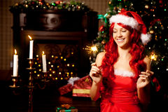 Young beautiful smiling santa woman near the Christmas tree. Gir Royalty Free Stock Image