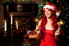 Young beautiful smiling santa woman near the Christmas tree. Gir. Young beautiful smiling santa woman near the Christmas tree. Fashionable luxury  girl Royalty Free Stock Images