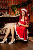 Young beautiful smiling santa woman near the Christmas tree. Gir Royalty Free Stock Images
