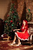 Young beautiful smiling santa woman near the Christmas tree. Gir Stock Photography