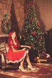 Young beautiful smiling santa woman near the Christmas tree. Gir Royalty Free Stock Photos