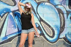 Young and beautiful smiling girl graffiti artist with gas mask on her neck hiding his eyes with a spray can. Standing on a wall background with a graffiti royalty free stock photo