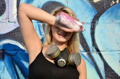 Young and beautiful smiling girl graffiti artist with gas mask on her neck hiding his eyes with a spray can. Standing on a wall background with a graffiti royalty free stock photos