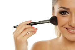Woman applying blush. Young beautiful smiling woman applying blush with a brush on a white background Stock Photos