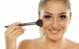 Woman applying blush. Young beautiful and smiling woman applying blush with a brush Royalty Free Stock Photo