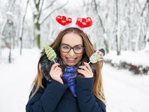 Young beautiful smiling young woman in christmas deer headpiece strolling in wintertime outdoor. Winter fun concept. Royalty Free Stock Image