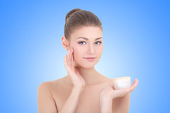 Young beautiful smiling woman with cream bottle over blue Stock Photography