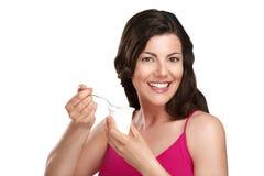Young beautiful smiling woman eating fresh yogurt. On white Royalty Free Stock Image