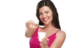 Young beautiful smiling woman eating fresh yogurt. On white Stock Photo