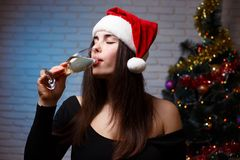 Young beautiful smiling woman in evening dress and Santa cap dri. Nking champagne from the glass on christmas tree background. New Year, Christmas, celebration Royalty Free Stock Image