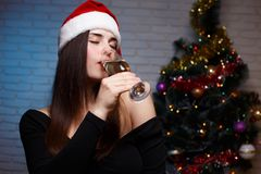 Young beautiful smiling woman in evening dress and Santa cap dri. Nking champagne from the glass on christmas tree background. New Year, Christmas, celebration Stock Images