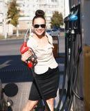 Young beautiful smiling woman fills petrol car Royalty Free Stock Photo