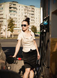 Young beautiful smiling woman fills petrol car Royalty Free Stock Photo