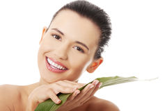 Young beautiful smiling woman with green leaf Royalty Free Stock Images
