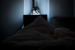 Young beautiful smiling woman lie in bed hold hands on laptop Royalty Free Stock Images
