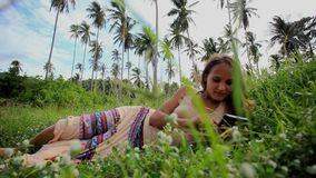 Young beautiful smiling woman lies on lawn and stock video footage