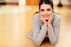 Young beautiful smiling woman lying on the floor Royalty Free Stock Image