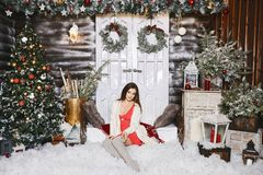 Young beautiful smiling woman near the Christmas tree. Beautiful luxury trendy brunette sits on stairs at Christmas royalty free stock photos