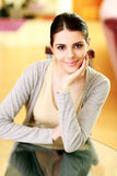 Young beautiful smiling woman sitting at the table Royalty Free Stock Photos