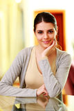 Young beautiful smiling woman sitting at the table Royalty Free Stock Images