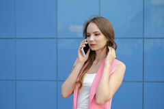 Young beautiful smiling woman talking on cell phone outdoors Stock Photography