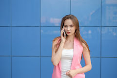 Young beautiful smiling woman talking on cell phone outdoors Royalty Free Stock Photography