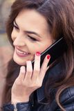 Young beautiful smiling woman talking on cellphone. In close up view royalty free stock images