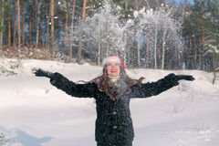Young beautiful smiling woman throwing snow in the air in winter holidays Royalty Free Stock Photography