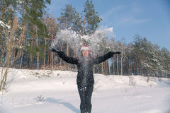 Young beautiful smiling woman throwing snow in the air in winter holidays Stock Photography