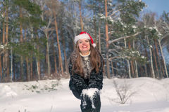 Young beautiful smiling woman throwing snow in the air in winter holidays Stock Photos