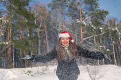Young beautiful smiling woman throwing snow in the air in winter holidays Stock Image