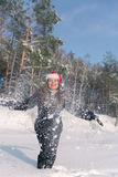 Young beautiful smiling woman throwing snow in the air in winter holidays Royalty Free Stock Photos