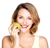Young beautiful smiling woman touches the apple to face. Stock Photo