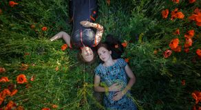Two women lay on poppy flower field Stock Images