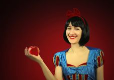 Young beautiful snow-white close-up keeps a red poisoned apple against the red background.  Stock Images