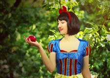Young beautiful snow-white close-up keeps a red poisoned apple against the background of trees in the forest.  Stock Photos