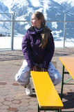 Young beautiful snowboarder woman sitting on the bench. Royalty Free Stock Image