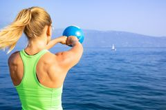Beautiful women man group are doing sport fitness cross at the lake with a kettlebell. Young beautiful sport woman is doing her cross workout at the water to get royalty free stock photos
