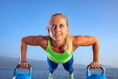Beautiful women man group are doing sport fitness cross at the lake with a kettlebell. Young beautiful sport woman is doing her cross workout at the water to get stock photo