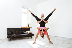 Young beautiful sportive couple practicing partner yoga asanas at home. Copy space Royalty Free Stock Image