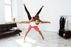 Young beautiful sportive couple practicing partner yoga asanas at home. Stock Images