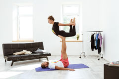 Young beautiful sportive couple practicing yoga asanas at home. Royalty Free Stock Photo