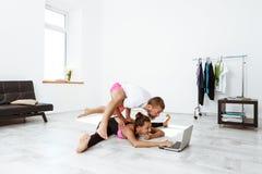 Young beautiful sportive couple training yoga asanas at home. Stock Photos