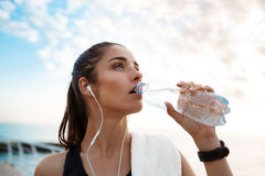 Young beautiful sportive girl drinking at sunrise over seaside. Young beautiful brunette sportive girl drinking water at sunrise over seaside. Copy space Royalty Free Stock Images