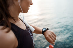 Young beautiful sportive girl looking at watch during sunrise over seaside. Royalty Free Stock Image