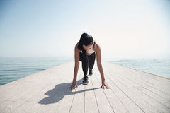 Young beautiful sportive girl preparing to run. Over seaside Royalty Free Stock Photography