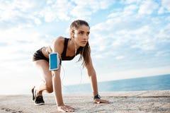Young beautiful sportive girl preparing to run over seaside. Stock Photos